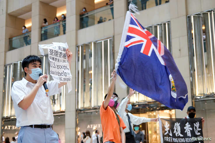 A pro-democracy demonstrator wearing a face mask waves the British colonial Hong Kong flag as another one holds a sign during a protest against new national security legislation in Hong Kong, China, June 1, 2020.