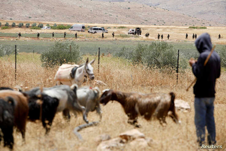 Israeli troops stand guard as Palestinians protest against Israel's plan to annex parts of the occupied West Bank, in Jordan Valley, June 5, 2020.