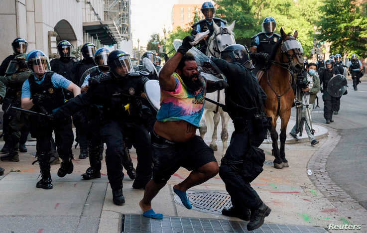Riot police chase a man as they rush protesters to clear Lafayette Park and the area around it across from the White House for President Donald Trump to be able to walk through for a photo opportunity in front of St. John's Episcopal Church, June 1, 2020.