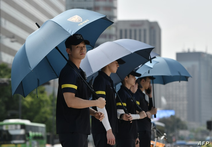 Police officers use umbrellas to protect themselves from the sun while anti-war activists hold a rally against planned South...