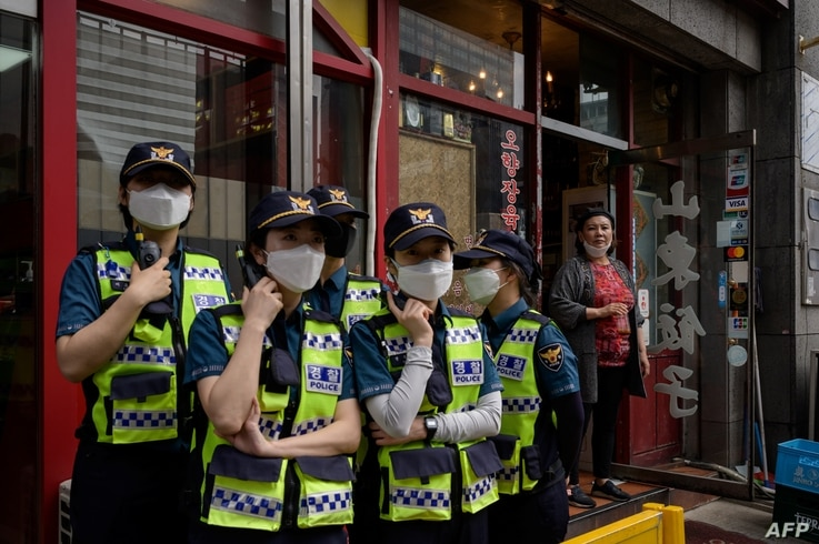 A woman stands at the door of a Chinese restaurant near China's embassy in Seoul as police officers monitor a group of pro…