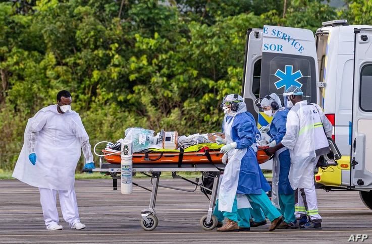 Medical staff carry a patient infected with the novel coronavirus (Covid-19) into an Airbus A400M at Guiana air-base 367 in…