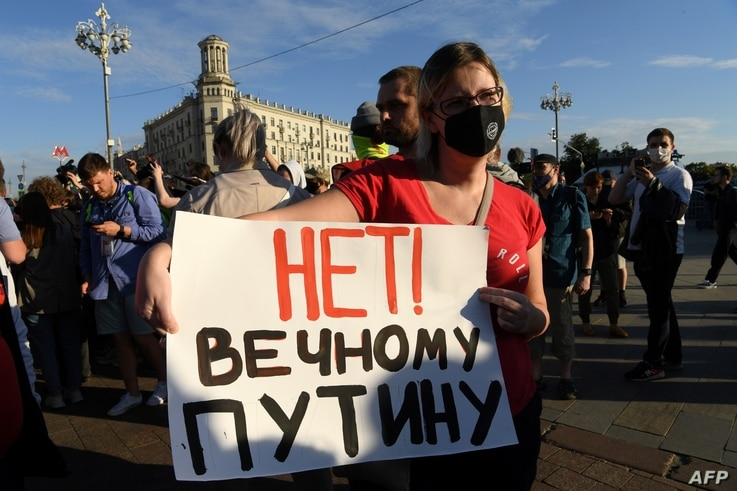 "A woman holds a placard reading ""No to everlasting Putin"" as she protests against amendments to the Constitution of Russia on…"