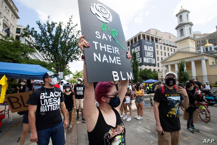 Demonstrators march near the White House and St, John's Church (R) ahead of the Fourth of July celebration on July 4, 2020, in…
