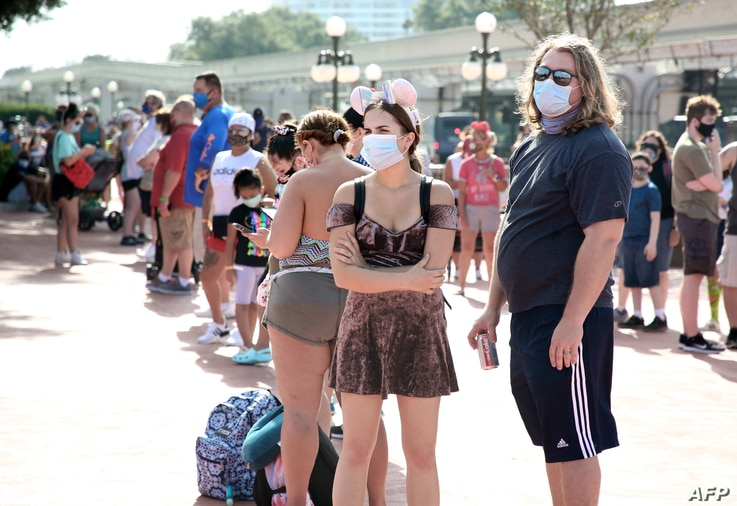 Guests wearing protective masks wait outside the Magic Kingdom theme park at Walt Disney World on the first day of reopening,…