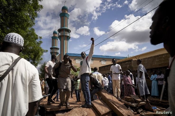 Protesters gestures on a barricade put up in front of the Salam mosque of Badalabougou, where the influent Imam Mahmoud Dicko…