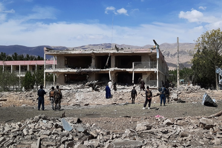 Afghan security personnel inspect the site of a car bomb blast near the destroyed office building of Afghanistan's intelligence…