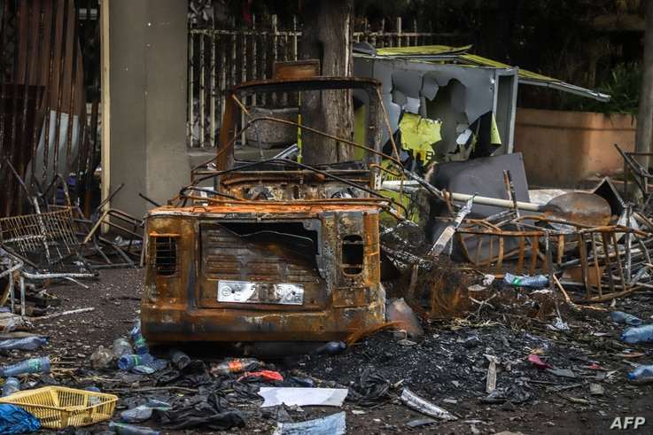 A burned car and bulding which were set on fire by a mob during the violence after the assasination of Oromo's pop singer…