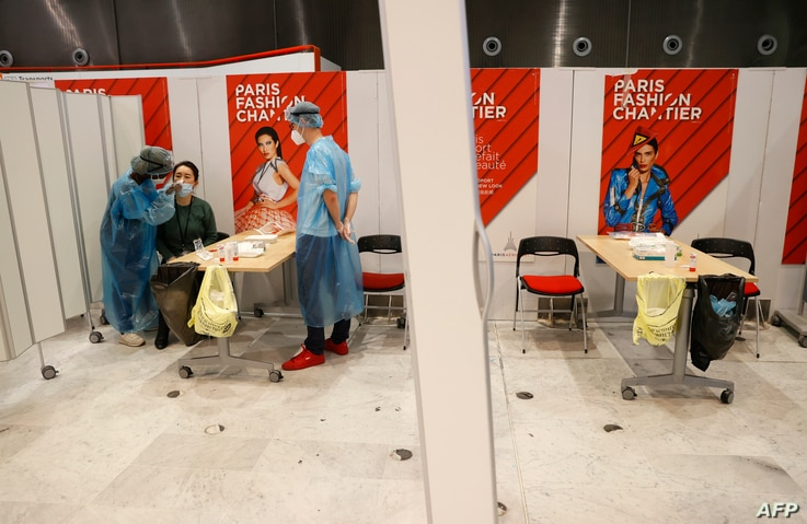 Healthcare workers wearing protective equipment gear collect a swab sample from a passenger at a COVID-19 (novel coronavirus)…
