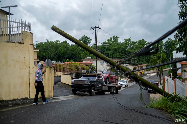 A man guides a tow truck under a downed power line pole after Tropical Storm Isaias affected the area in Mayaguez, Puerto Rico…