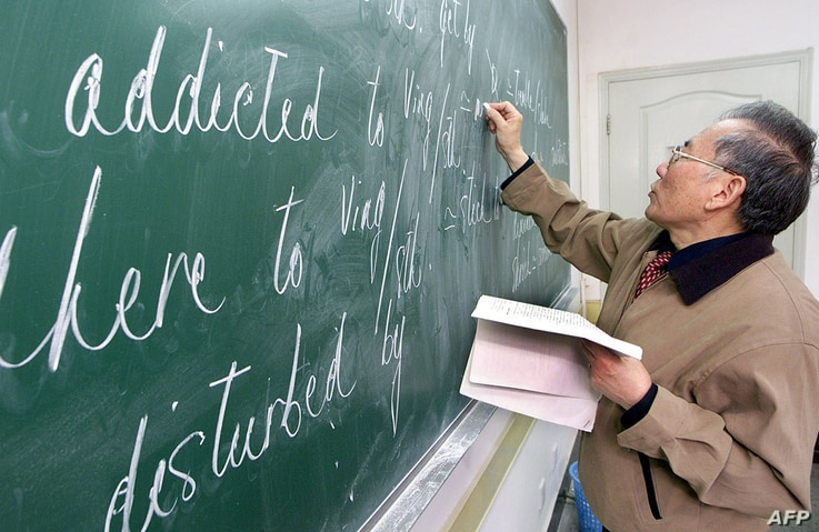 A Chinese teacher writes English words on a black board at a class in Shanghai, 26 April 2002. Chinese desperate to improve…