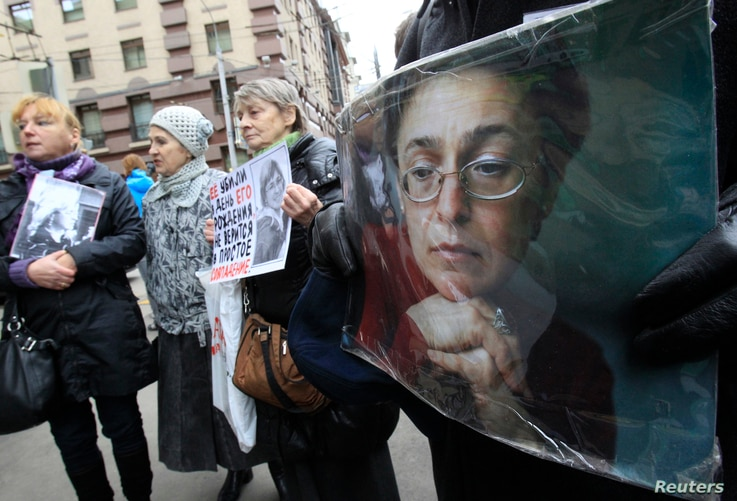 People hold portraits of slain journalist Anna Politkovskaya on the sixth anniversary of her death, next to her block of flats…