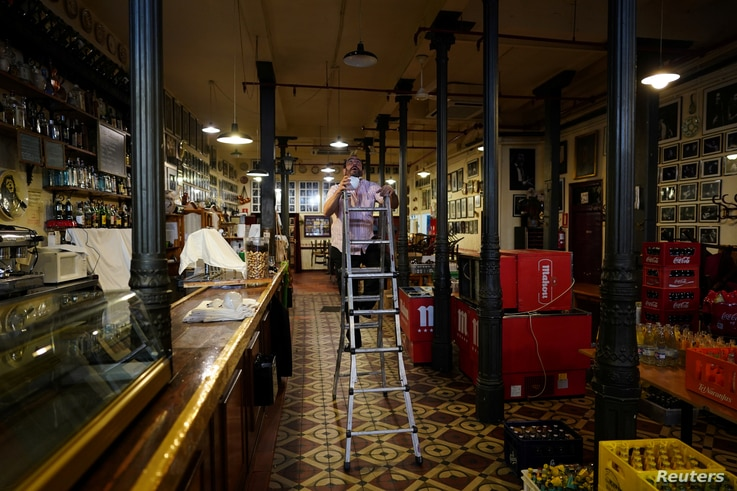 Martin Guerrero, general director of tavern-restaurant and flamenco tablao Casa Patas, climbs a ladder to change a light bulb…