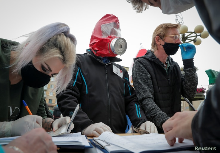 Opposition supporters wearing protective masks amid the coronavirus disease outbreak put signatures in support of…