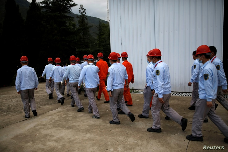 Staff members walk at Xichang Satellite Launch Center, the day before the Beidou-3 satellite, the last satellite of China's…