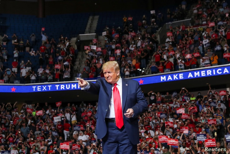 U.S. President Donald Trump points at the crowd as he enters his first re-election campaign rally in Tulsa, OK.