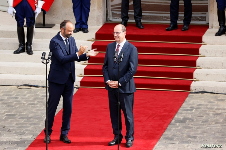Former French Prime Minister Edouard Philippe applauds newly-appointed Prime Minister Jean Castex in the courtyard of the...