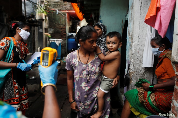 A healthcare worker checks the temperature of residents of a slum area using an electronic thermometer, in Mumbai, India, July 6, 2020.