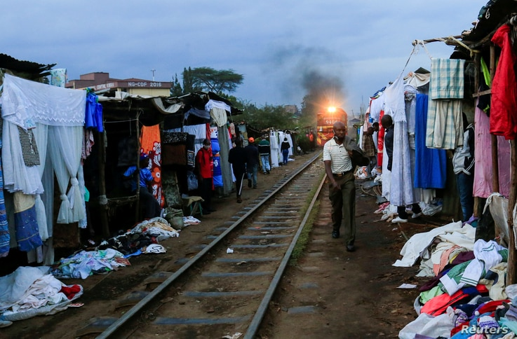 A man walks along a railway line as a commuter train approaches, amid the spread of the coronavirus disease (COVID-19), at the…