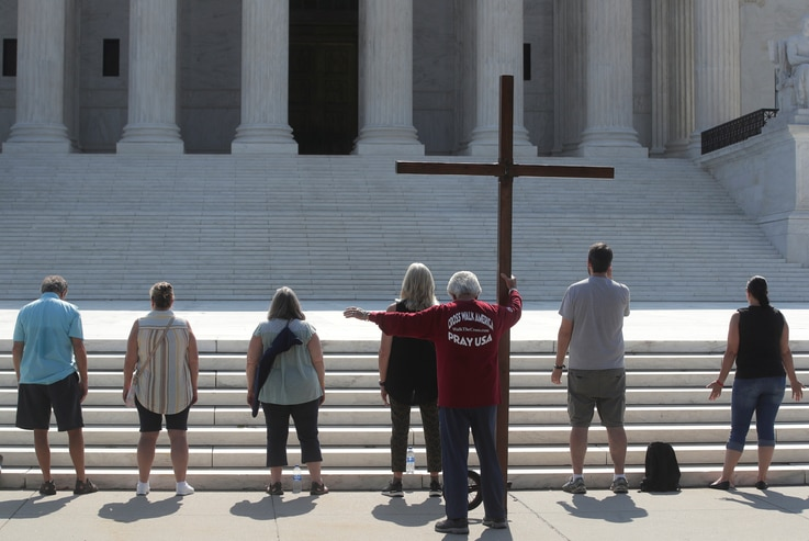 Demonstrators gather outside the U.S. Supreme Court as the court ruled that religious institutions like churches and schools…