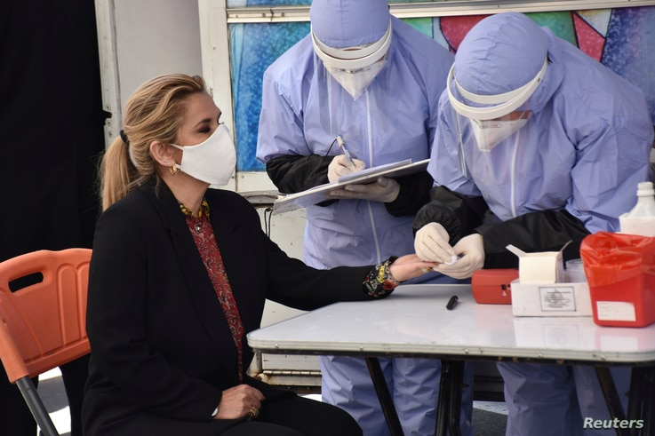 Healthcare workers conduct a blood test on Bolivia's Interim President Jeanine Anez during the World Blood Donor Day campaign…