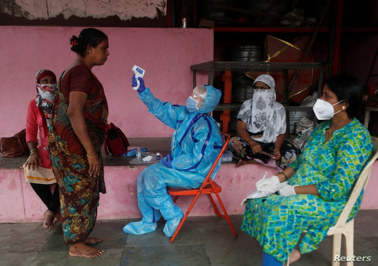 A health worker in personal protective equipment (PPE) checks the temperature of a resident with an electronic thermometer…