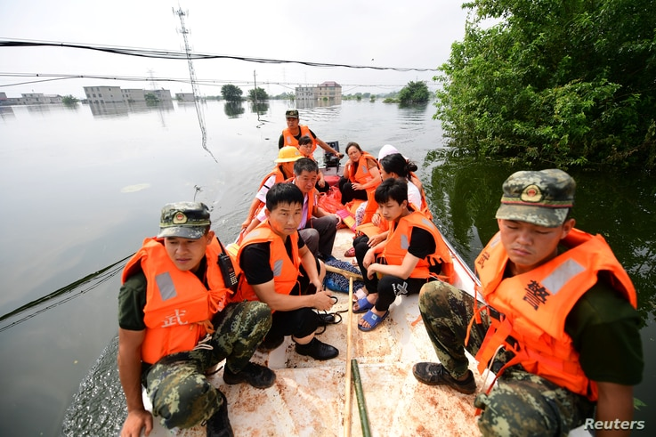 Paramilitary police officers evacuate residents from a flood-hit village with a boat in Yongxiu county of Jiujiang, Jiangxi…