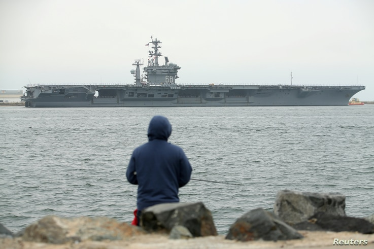 FILE PHOTO: Sailors man the rails as aircraft carrier USS Nimitz with Carrier Strike Group 11, and some 7,500 sailors and…