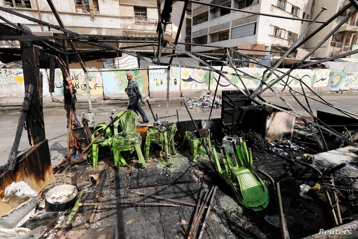A man walks past the remains of a tent, which was burnt last night during the ongoing anti-government protest due to poor…