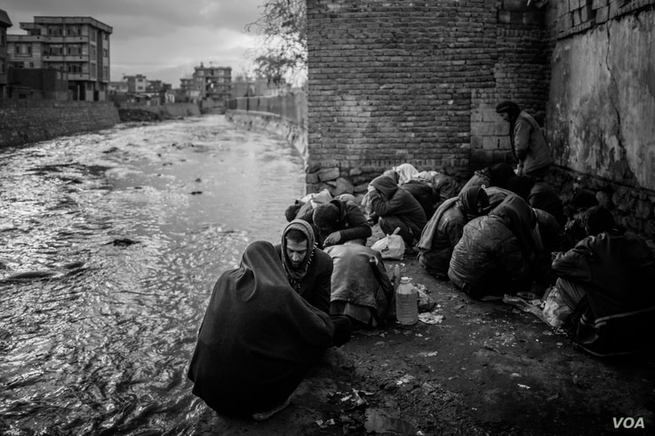 Drug users at a riverbank in Kabul