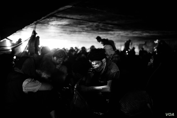 Even during the day, it is often dark under the bridge in Pul e Sukhta. A man with a head torch prepares his drugs