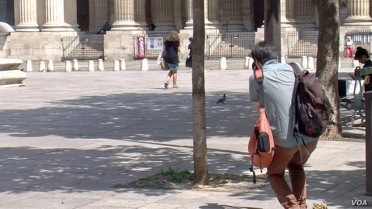 A visitor snaps a picture of Saint Sulpice church in Paris.  (photo by Lisa Bryant)