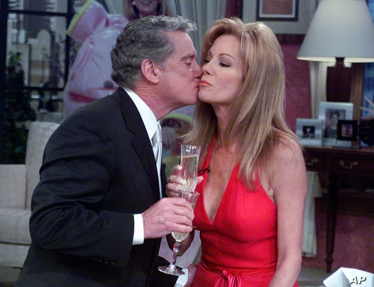 Co-hosts Regis Philbin and Kathie Lee Gifford share a toast of champagne at the end of her last appearance on their morning…
