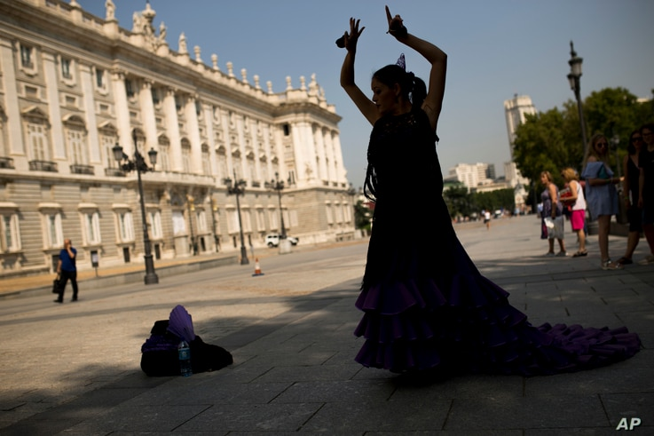 A street artist wearing a flamenco dress performs in front of the Royal Palace in Madrid, Friday, Sept. 8, 2017. The future of…