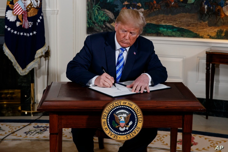 President Donald Trump signs a Presidential Memorandum on the Iran nuclear deal from the Diplomatic Reception Room of the White…