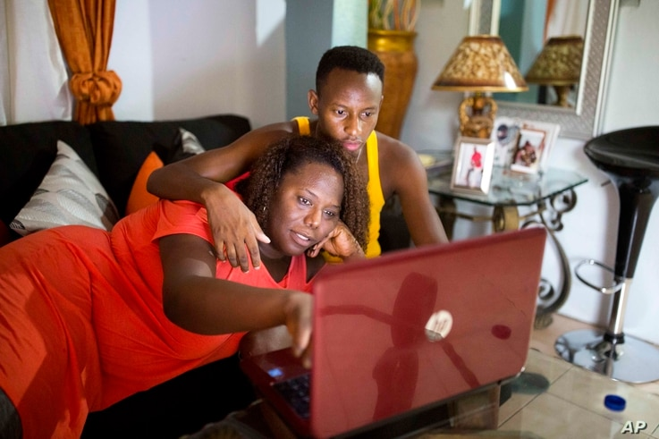 Yaisah Val, 46, a transgender woman, watches a movie with her husband, Richecarde Val, 28, in their home in Port-au-Prince.