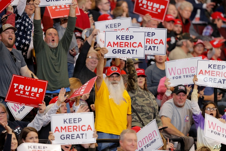 Supporters hold up signs as President Donald Trump speaks at a campaign rally in Bossier City, La.