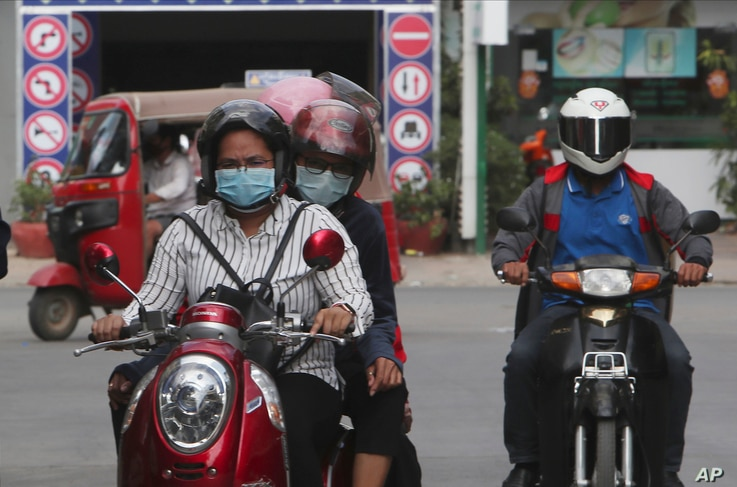 In this Friday, April 3, 2020, photo, motorists wear face masks to protect against the spread of the coronavirus in Phnom Penh,…