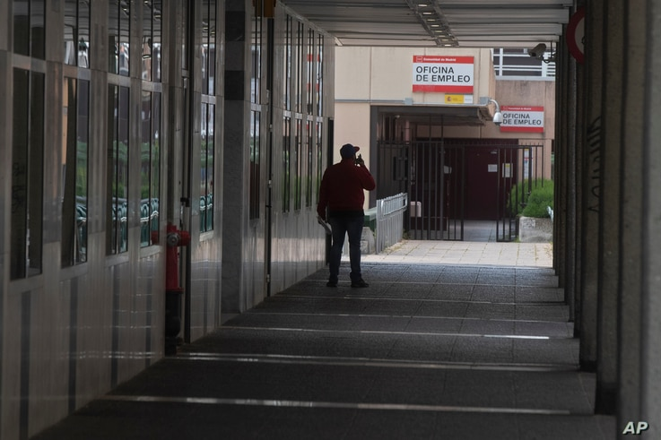 A man speaks on his phone outside an unemployment office in Madrid, Spain, April 27, 2020.