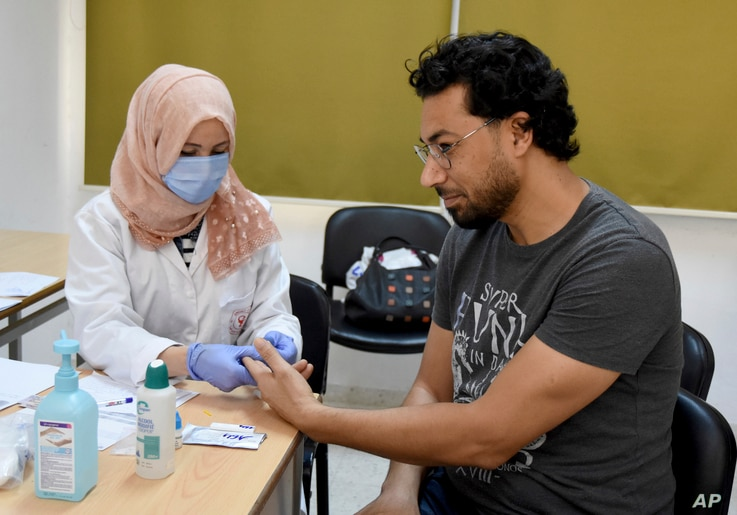An employee of the Tunisian Health ministry takes a blood sample to test a teacher against the COVID-19 in a school of Tunis,…