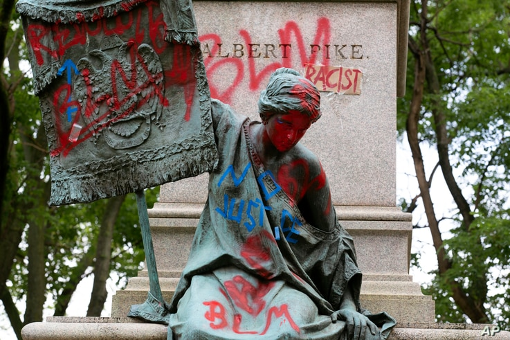 Defaced bronze sculpture on the base of the statue of Confederate general, Albert Pike, after protestors toppled Pike statue, June 20, 2020, in Washington.