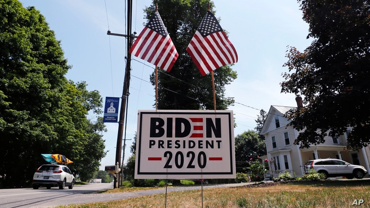 A car passes a yard displaying a campaign sign for Democratic presidential candidate, former Vice President Joe Biden, June 23, 2020 in North Hampton, New Hampshire.