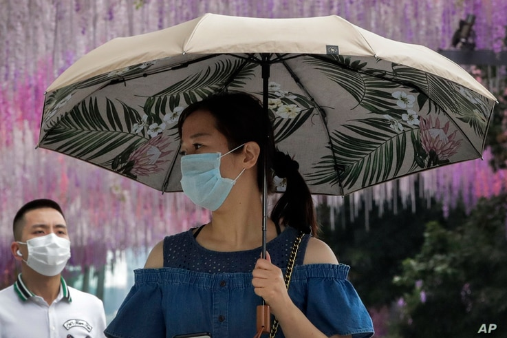 People wearing face masks to help curb the spread of the coronavirus walk by a decoration outside a shopping mall in Beijing.