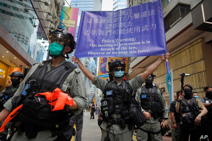 Police display a public announcement banner showing the warning to protesters in Causeway Bay before the annual handover march…
