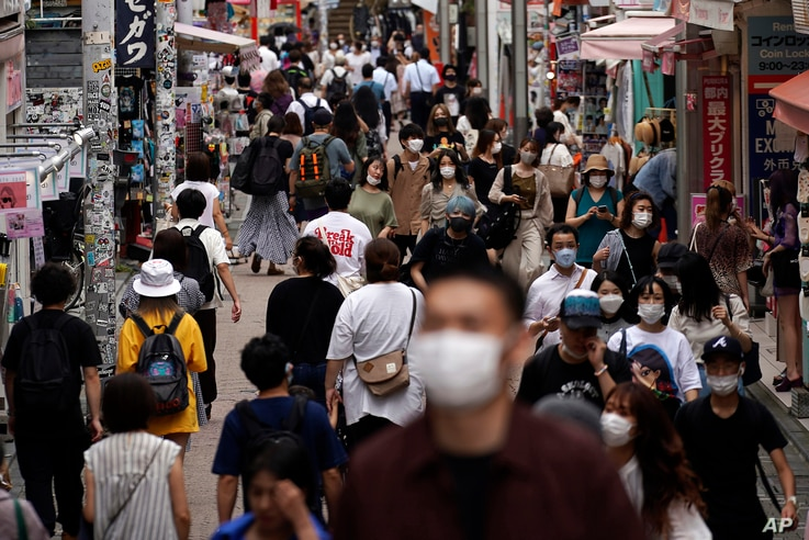 People wearing face masks to help curb the spread of the coronavirus walk through a shopping street in Tokyo, Friday, July 3,…