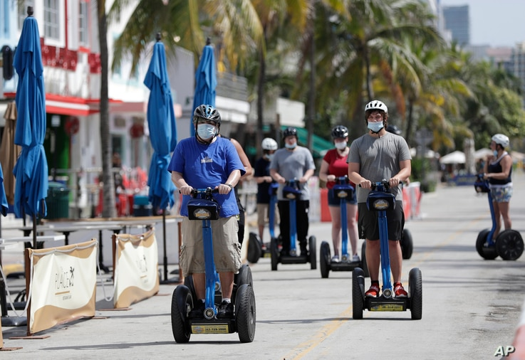 A tour group riding Segways rides down Miami Beach, Florida's famed Ocean Drive on South Beach, July 4, 2020. The Fourth of…
