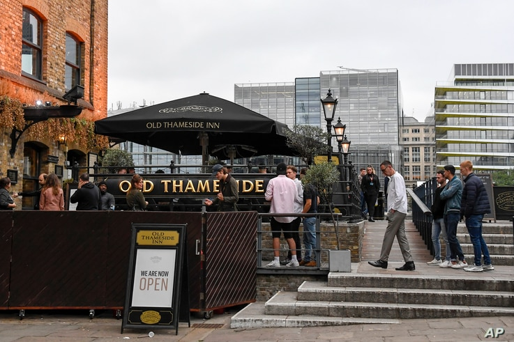 People sit and drink, outside a pub on the south bank of river Thames, as the capital is set to reopen after the lockdown due to the coronavirus outbreak, in London, July 4, 2020.