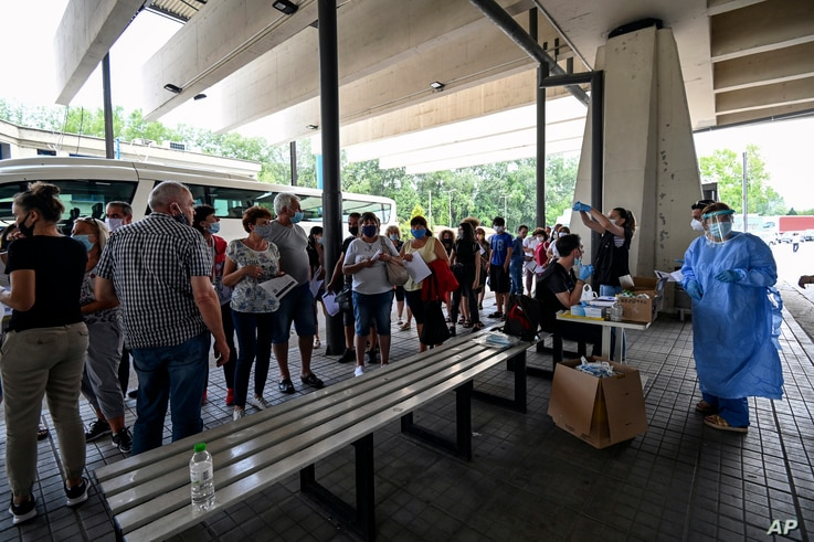 Health worker wearing protective gear against coronavirus give instructions to tourist at Promahonas border crossing with…