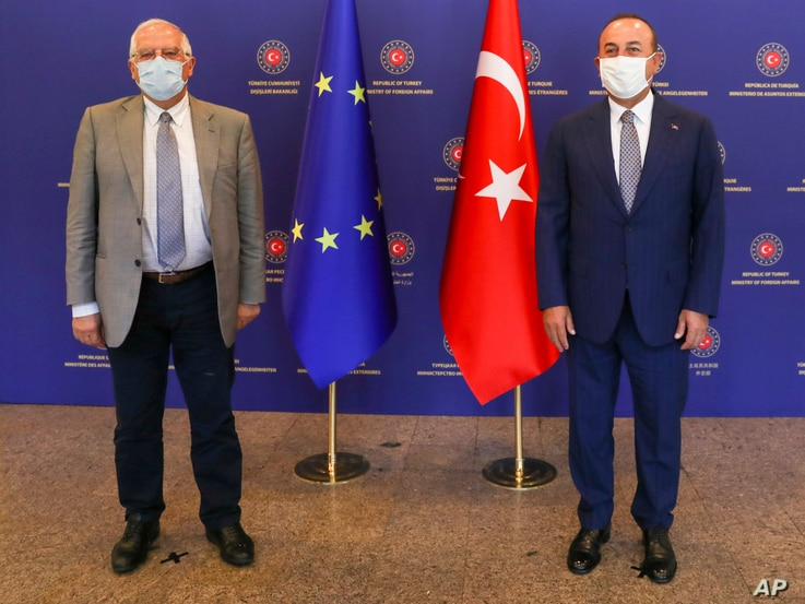 Turkey's Foreign Minister Mevlut Cavusoglu, right, and Josep Borrell Fontelles, High Representative and Vice-President of the European Commission, pose for photos before a meeting, in Ankara, Turkey, July 6, 2020.
