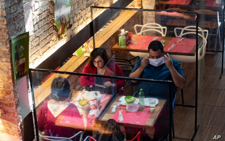 People eat lunch at a restaurant with plastic dividers between tables, as a preventative measure amid the COVID-19 pandemic in…